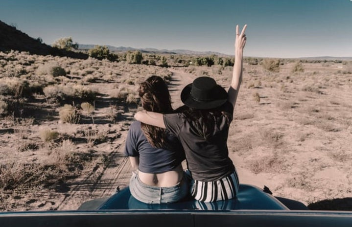 Two girls sitting back faced on a car