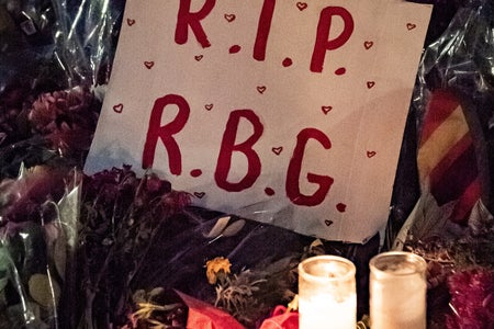 A poster saying R.I.P R.G.B laying on flowers and candles at Ruth Bader Ginsberg's memorial.