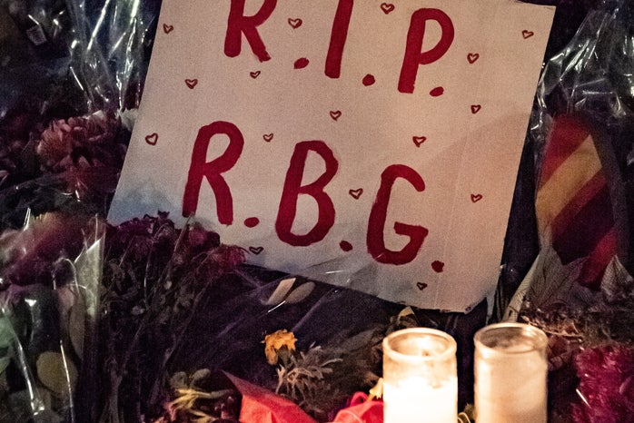 A poster saying R.I.P R.G.B laying on flowers and candles at Ruth Bader Ginsberg\'s memorial.