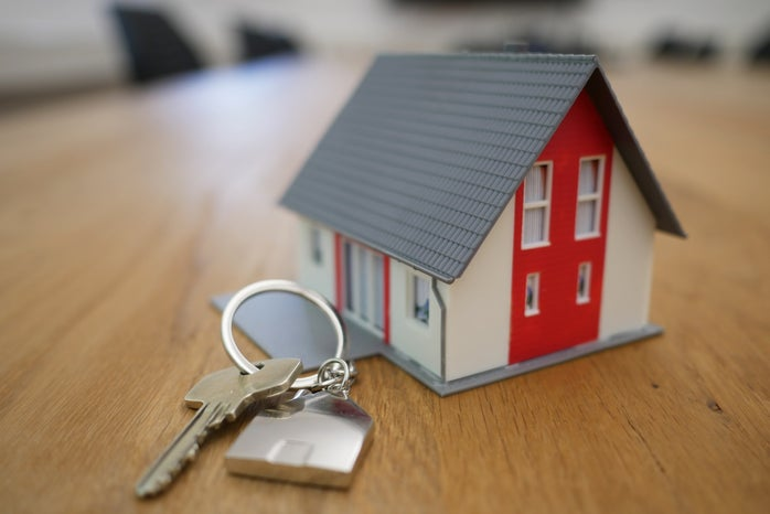 small house model and house key to represent real estate career