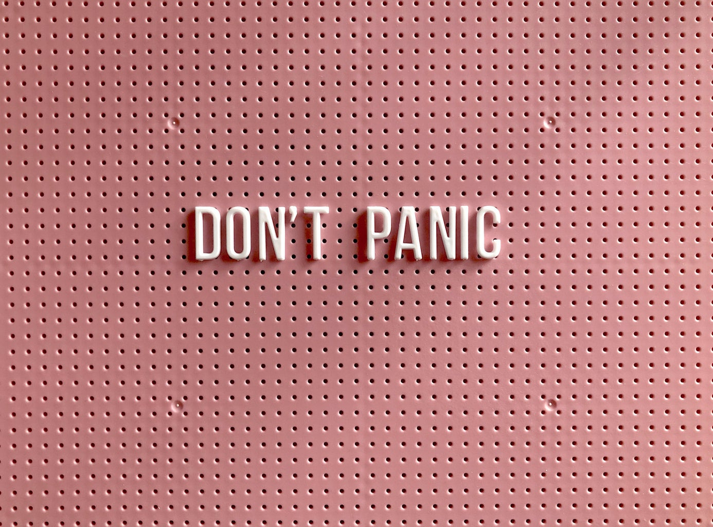 """A pink sign that says \""""don\'t panic\"""""""