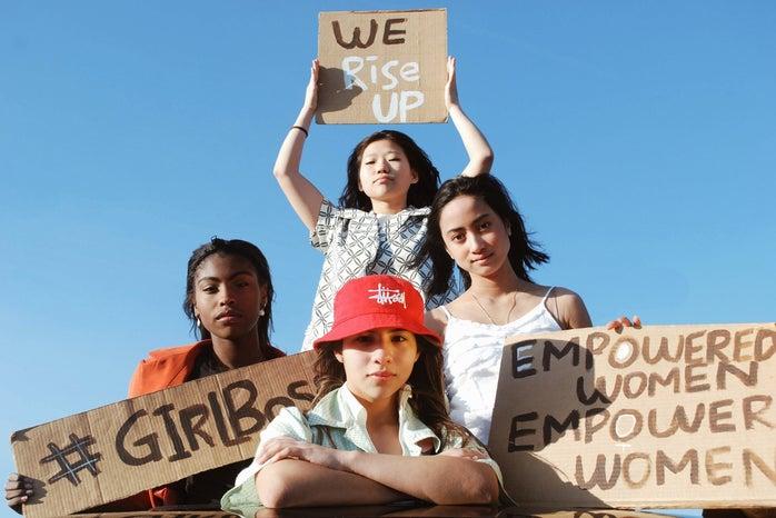 3 women holding cardboard signs