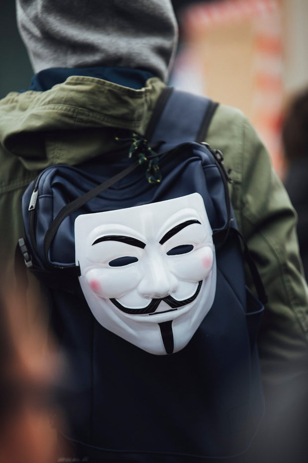 guy fawkes mask hanging off a backpack
