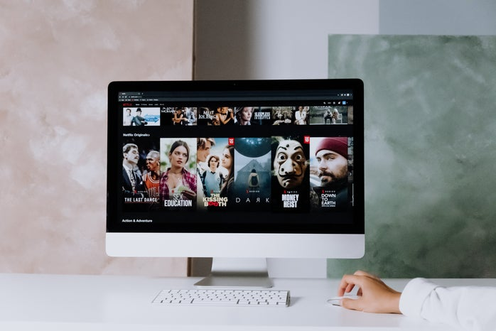 computer screen sitting on a white desk with Netflix shows on the screen