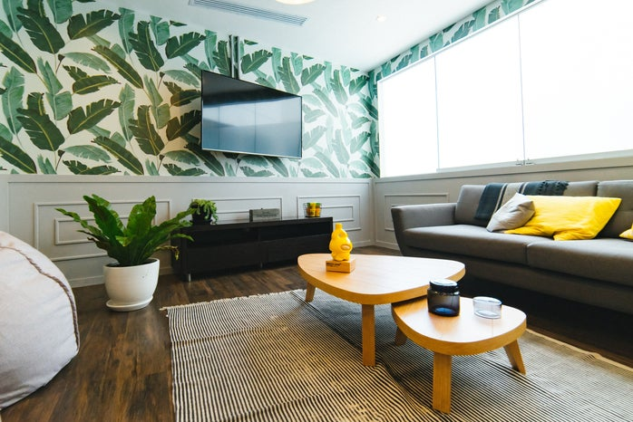 living room with gray couch and plant wallpaper