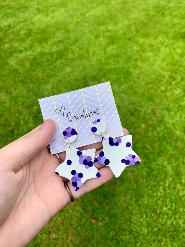 hand holding purple and white star earrings