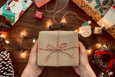 hands holding a wrapped present surrounded by lights and gifts