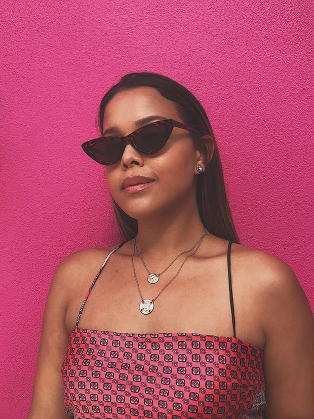 Woman wearing black and red sunglasses against a pink background
