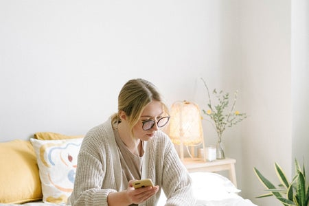 Woman sits studying on her bed. She is on her laptop and holding a phone.
