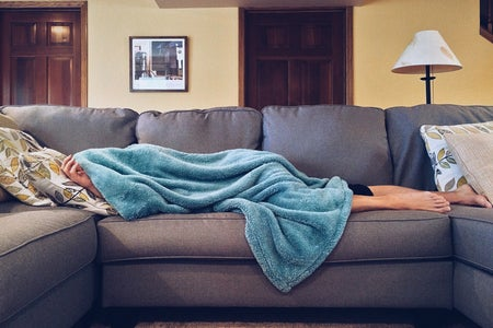Woman laying down on a couch covered in a blanket.