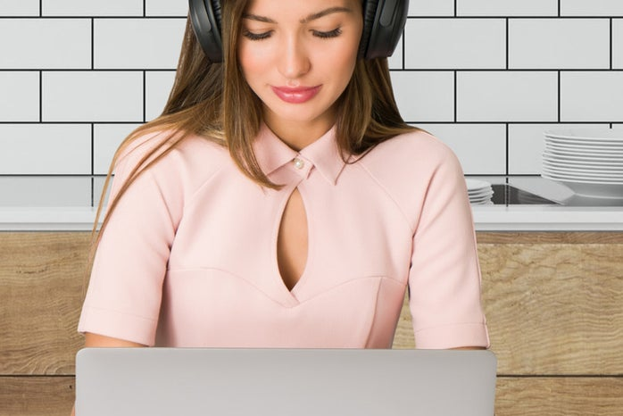 A woman (pink blouse) looking at her laptop while wearing headphones