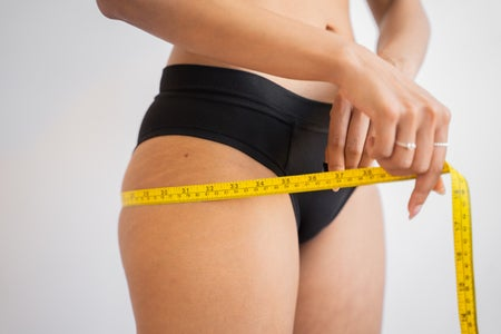 woman measuring her hips with a yellow measuring tape