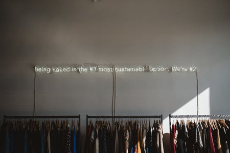 racks of clothing against a wall with a slogan written above them
