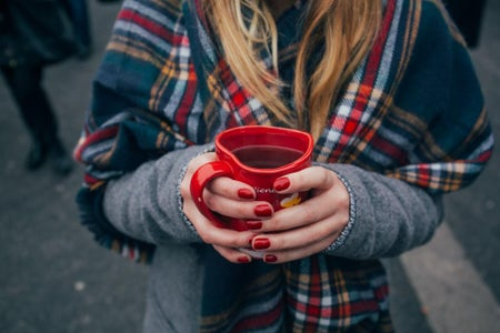 Girl with red manicure holding a red mug. She is wearing a plaid scarf. Fall vibes, cozy.