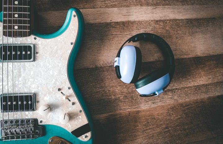 headphones next to a guitar