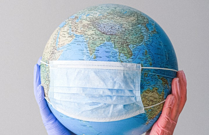 hands with latex gloves holding globe wearing a mask