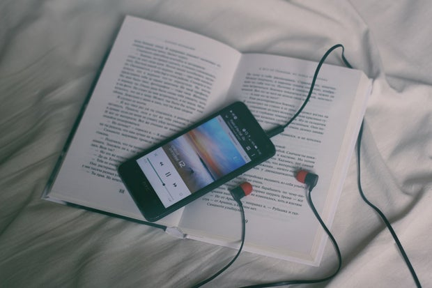open book placed on white sheets with a phone playing music through headphones