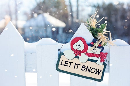 "a sign that says ""let it snow"" with snowmen are displayed on white fence."