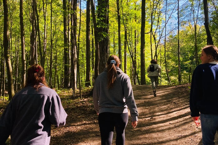 Girls hiking on trail in forest