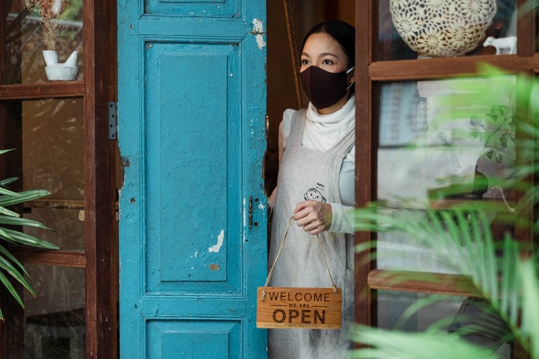 """Woman wearing mask holding """"Open"""" sign"""