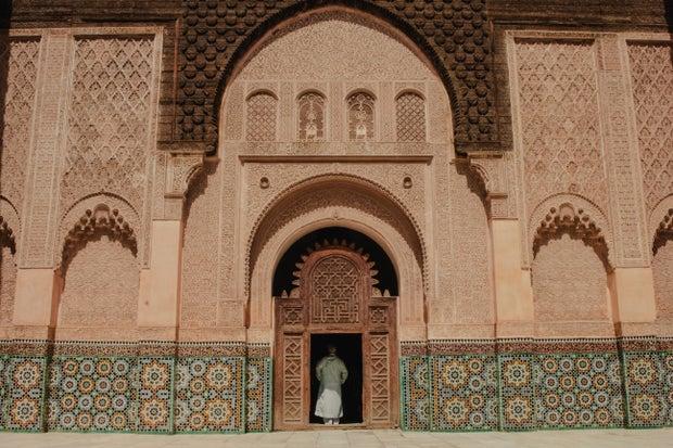 person standing on open door of building in Marrakesh, Morocco