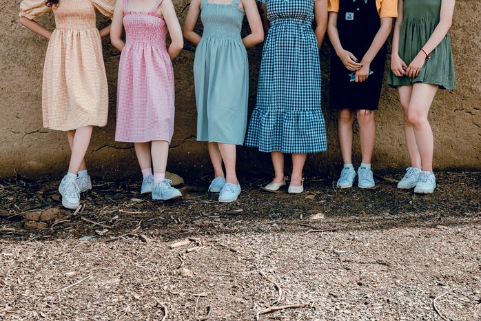 six women standing on dirt path