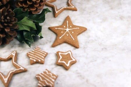 Christmas star cookies and pine cones on a marble table