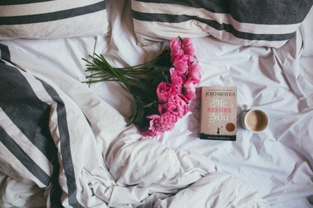 bouquet of pink flowers on a bed with a book