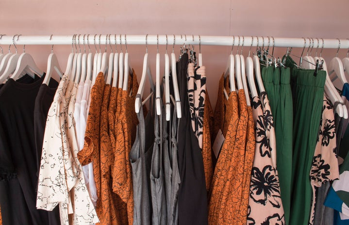 A clothing rack with various warm-toned outfits