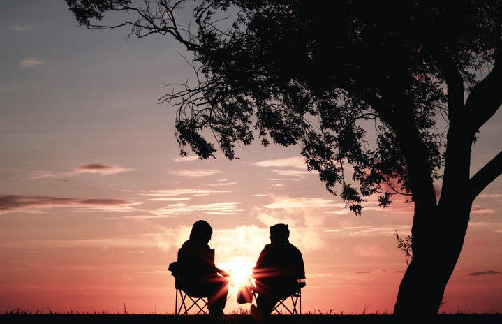 Two silhouettes against a backdrop of an orange-blue sunset are sitting in foldable camping chairs. There\'s a large tree to their right and above them.