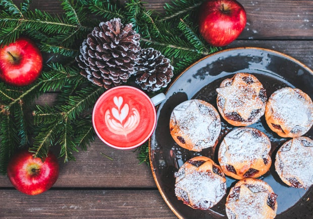 sweet pastries on black ceramic plate beside red latte, apples and pinecones
