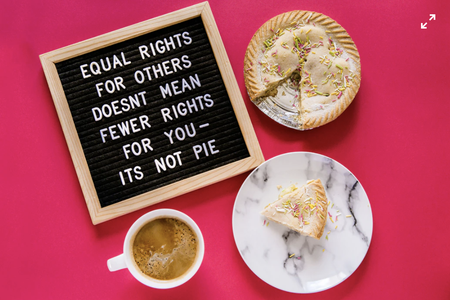 White ceramic plate with pie, coffee in a mug and a sign saying ' equal rights for others doesn't mean fewer rights' on a pink background