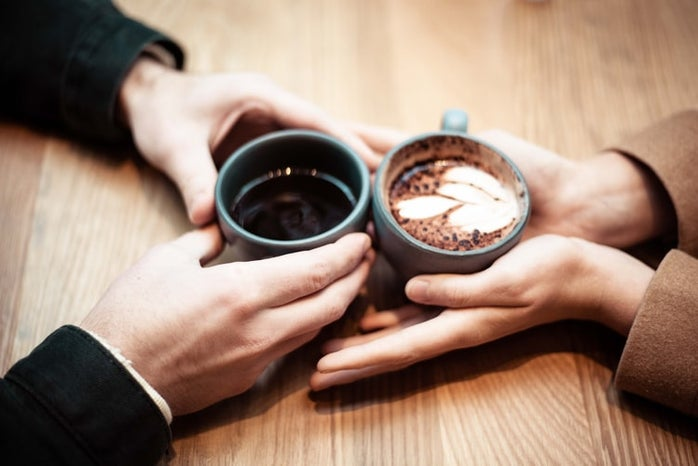 two people holding coffee mugs on table