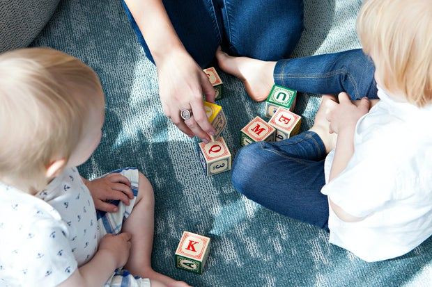 two toddlers playing with letter blocks