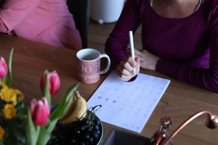 Woman writing at desk.