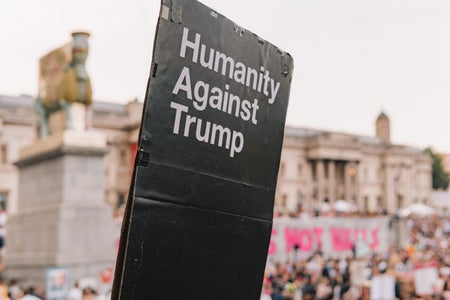 "person holding a sign that says ""humanity against Trump"""