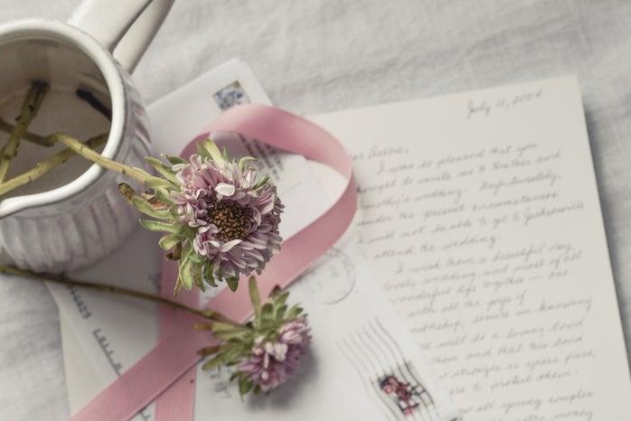 flowers in vase over handwritten letter