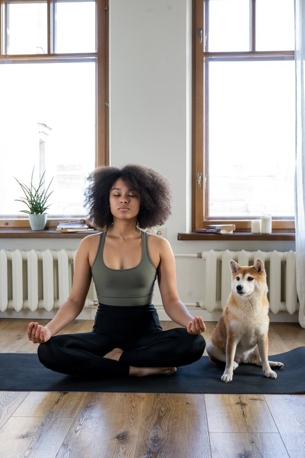 woman meditating with dog beside her