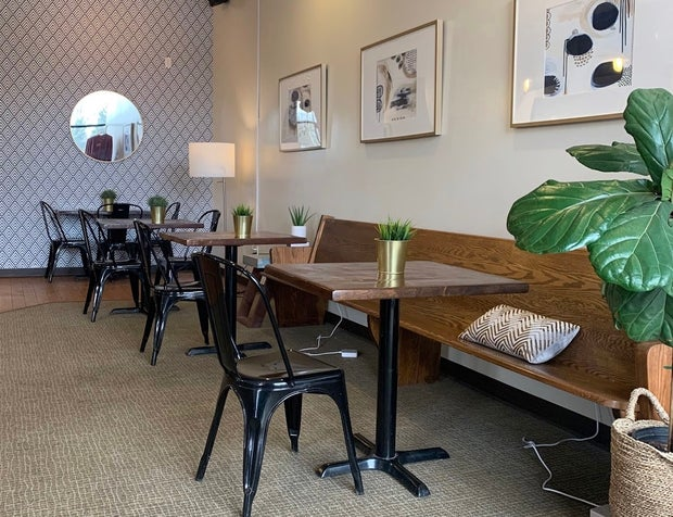 Wooden tables, black metal chairs, greenery, patterned back wall (The Spot)