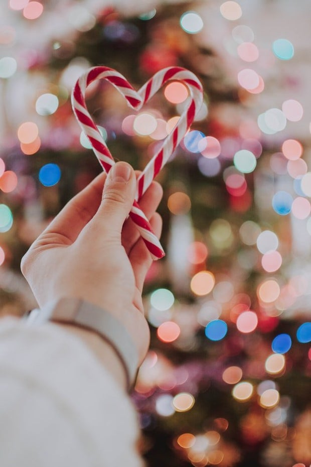 candy cane heart with a christmas tree in the background