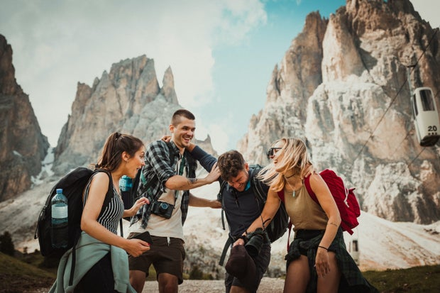 Two men and two women wearing backpacks laughing in front of mountains