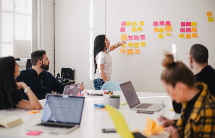 Woman placing sticky notes on wall in office meeting