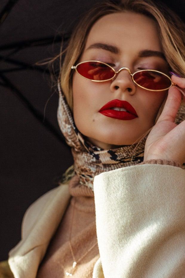 Fashionable young woman adjusting sunglasses on street