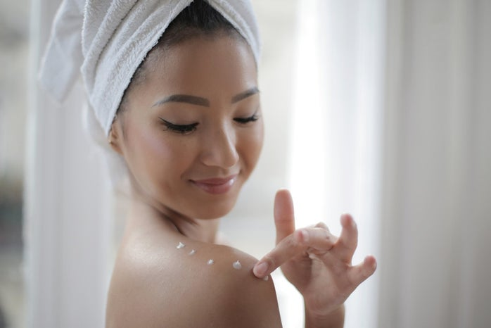 woman with towel on her head using lotion on shoulders