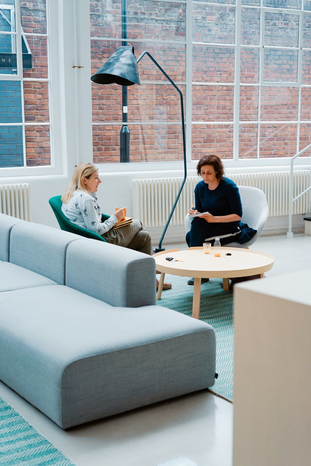 Two women sitting on a sofa at work