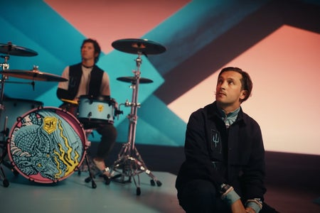 One man sitting down and another one playing the drums