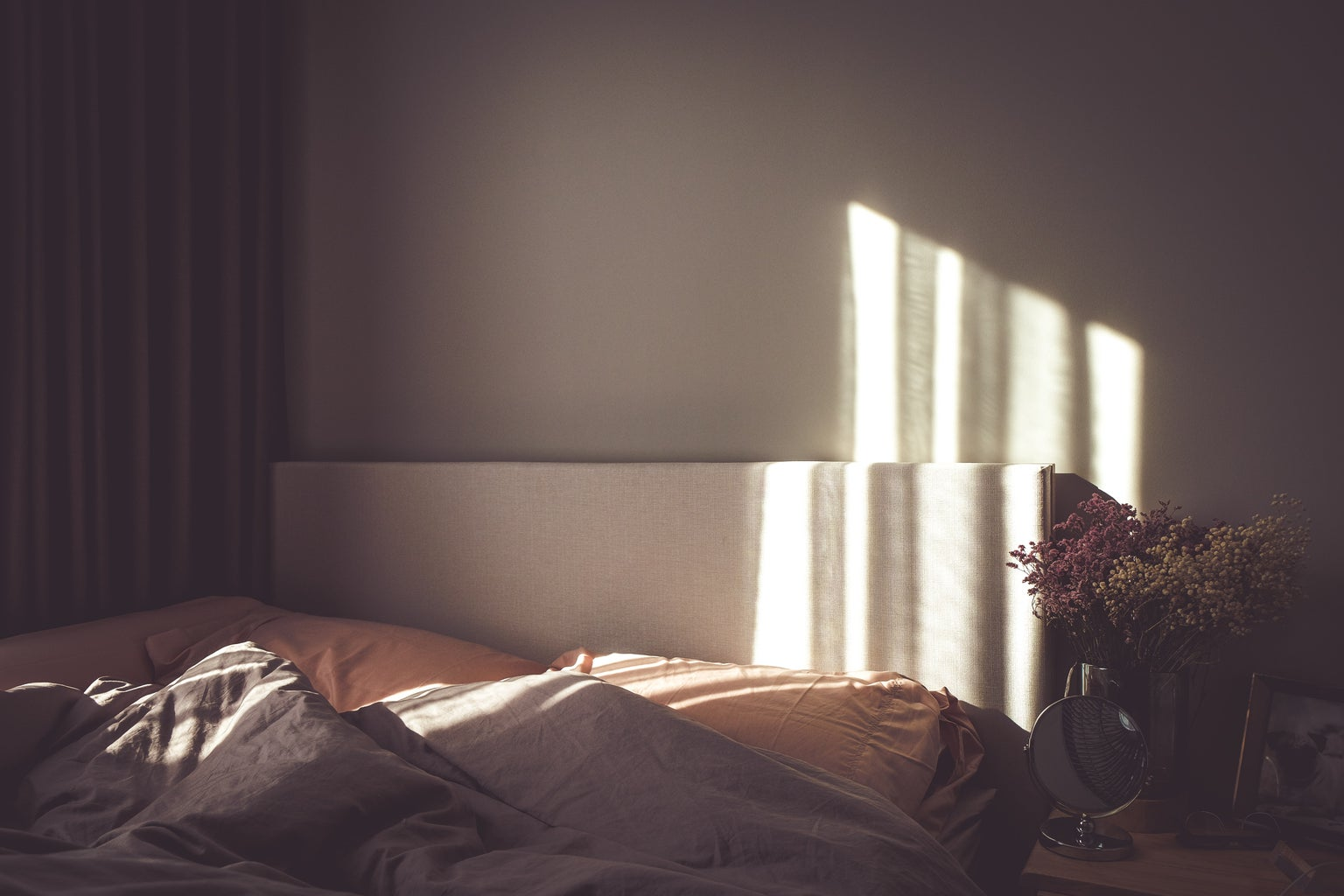 empty bed with sunlight on wall