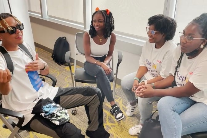 Cordae sitting with Howard University student journalists after the Kickin\' It With Cordae event.