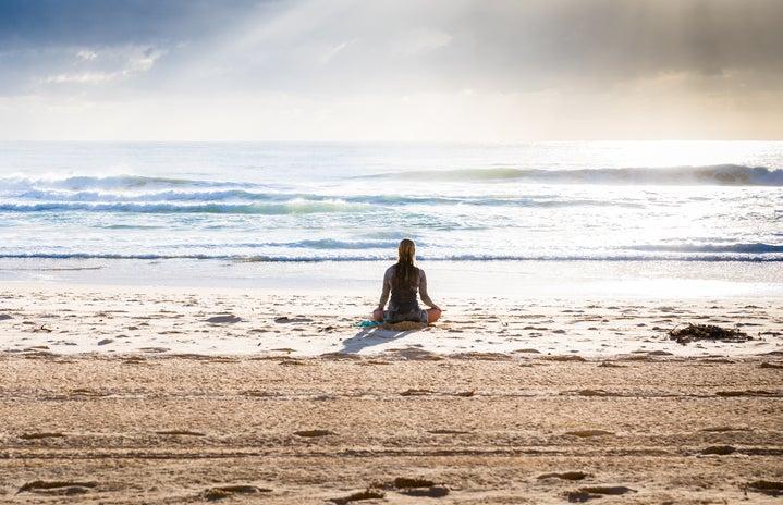 woman meditating on the beach