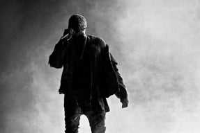 Kanye West performing on stage with face covering.
